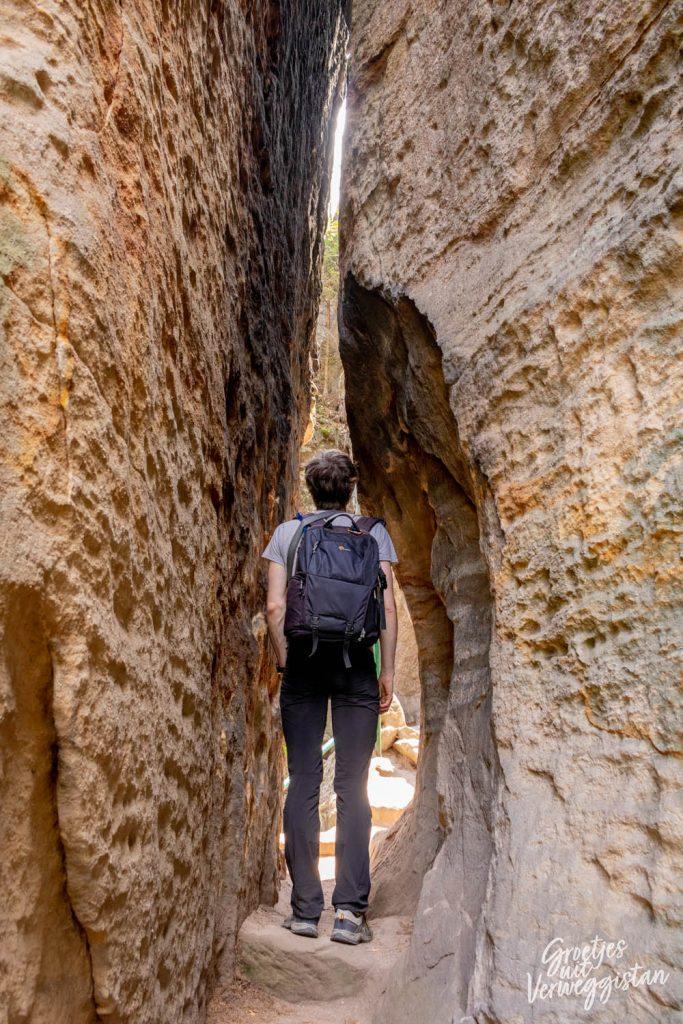Man met rugzak staat in een spleet tussen twee rotsen in Tsjechië.