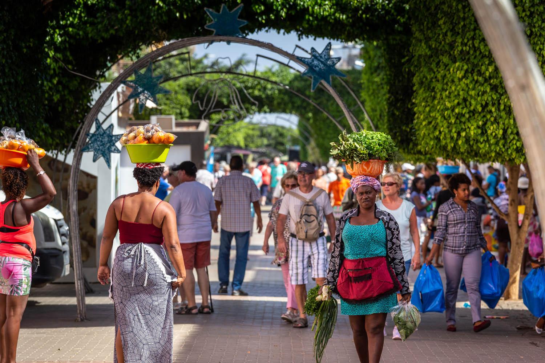 Vrouwen in Praia komen net van de markt en dragen de boodschappen in teilen op het hoofd.