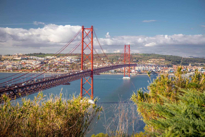 De rode stalen brug Ponte de 25 Abril over de rivier Taag richting Lissabon.