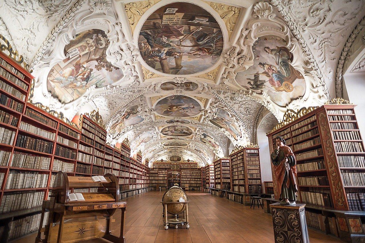 De prachtige bibliotheek van het Strahov klooster in Praag met een indrukwekkende schildering op het plafond en rijen boeken langs de muren.