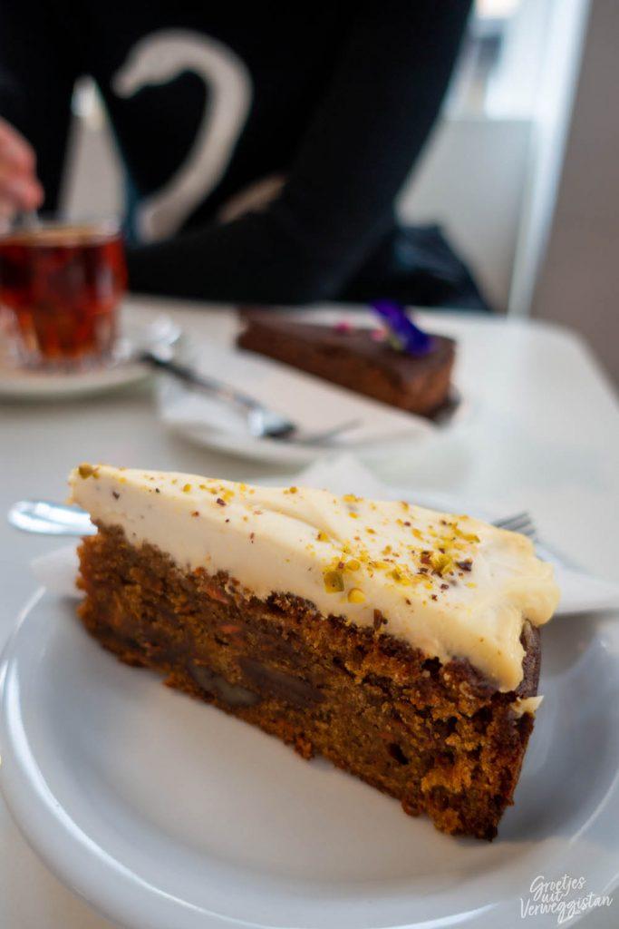 Worteltaart met dikke laag roomkaasfrosting bovenop met op de achtergrond chocoladetaart en thee in Blossom in Den Haag.