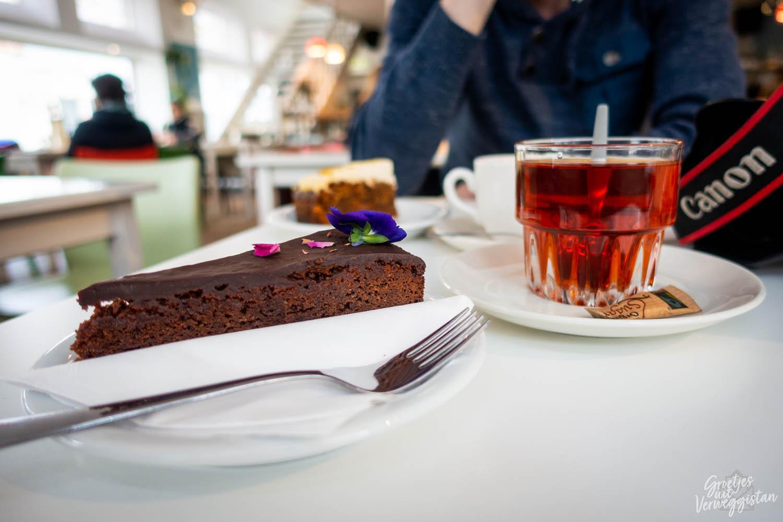 Chocoladetaart met eetbare paarse bloem erop en een kop thee met suiker bij Blossom in Den Haag.