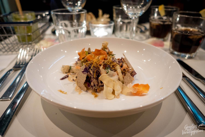 Gerecht met gedroogde producten zoals bloemen, miso en cashews op een wit bord bij Instock in Den Haag.