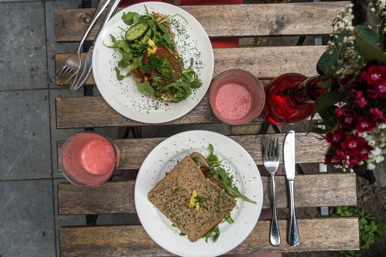 Lunch bestaande uit belegde broodjes en rode smoothies van bovenaf genomen in Juni Café in Den Haag.