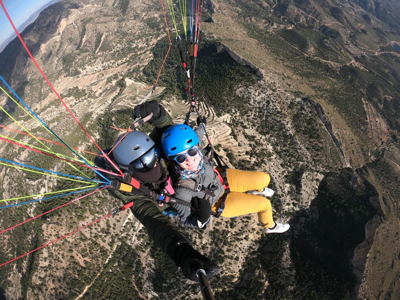 Foto vanboven genomen van Manouk en Juan die onder de parachute hangen tijdens het paragliden.