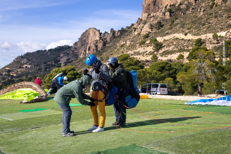 Maria checkt of Manouk goed vast zit voor de tandem paraglide door de gespen op haar benen te controlen.
