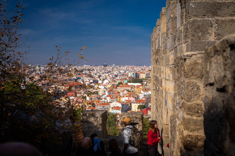 Rechts een klein stukje van een toren van het Castelo de São Jorge. Op de achtergrond de stad en vooraan een handje vol mensen dat zich over de muur van het kasteel begeeft