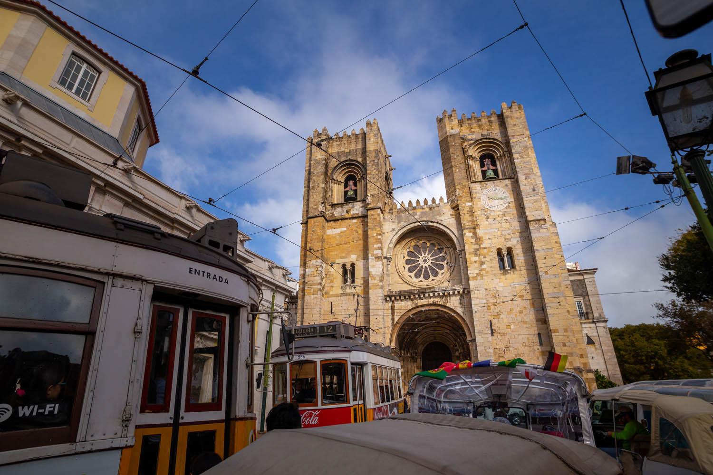 Grote drukte voor de kathedraal Sé de Lisboa: 2 trams en zeker 5 tuk-tuks proberen zich een weg te banen. Daarachter het vooraanzicht van de kathedraal: 2 stompe klokkentorens en een groot rond raam in midden.