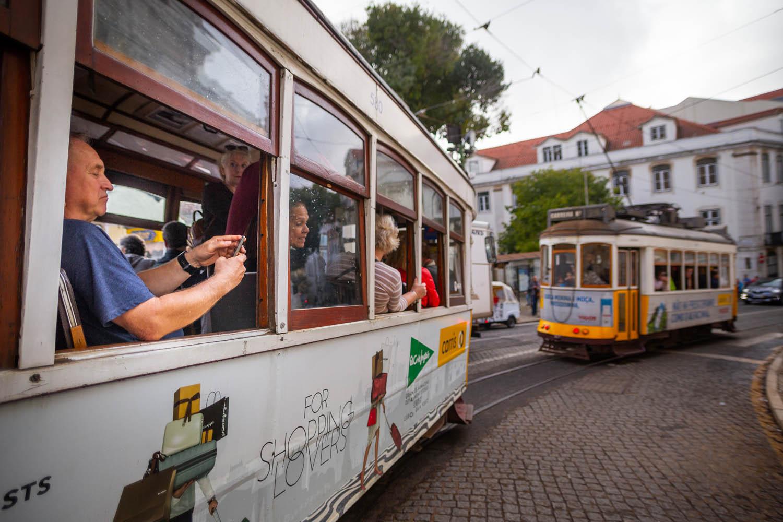 2 typisch gele trams in Lissabon. Beide gevuld met toeristen. Op de voorgrond iemand die uit het open raam een foto probeert te maken met zijn mobiele telefoon.