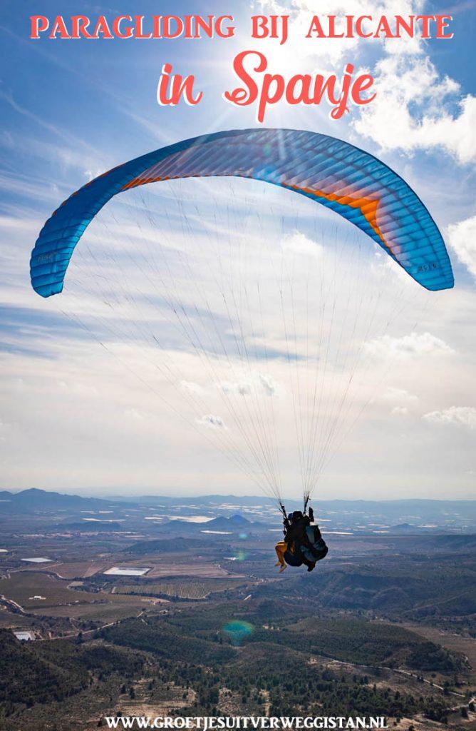 Pinterestafbeelding: Paragliding bij Alicante in Spanje met een foto van een paraglider met Alicante en Middellandse Zee op de achtergrond.