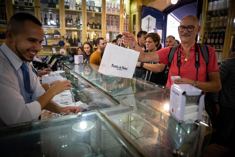 Veel mensen bij de toonbank in de winkel Pastéis de Belém, waar net een tasje vol pasteitjes overhandigd wordt.