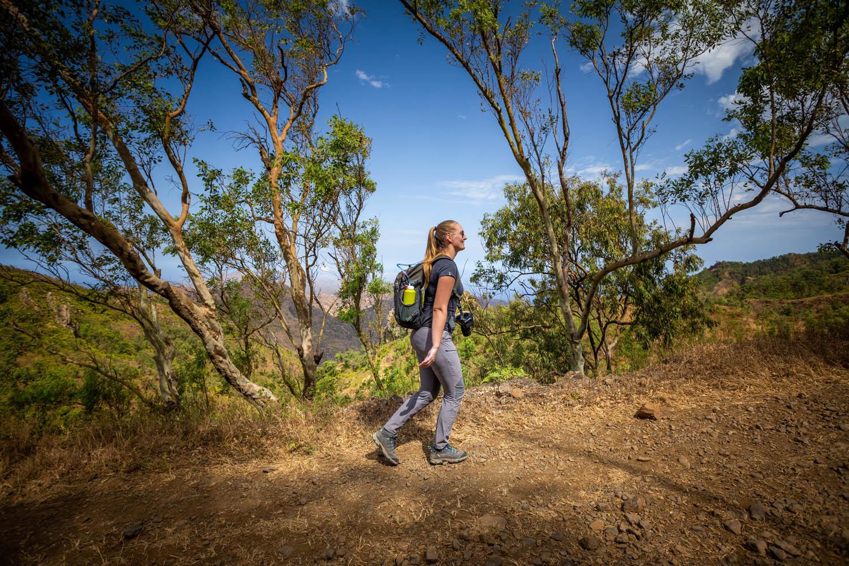 Manouk loopt met dagrugzak over een pad in Serra Malagueta op Santiago, vanaf de zijkant gezien.