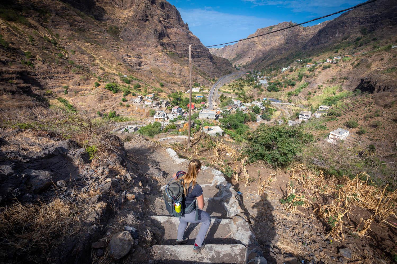 Manouk daalt een trap af, beneden zie je het dorpje Hortelão liggen aan een weg.