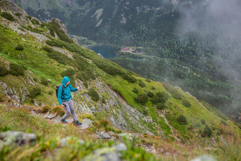 Manouk loopt in een turkoois regenjas naar beneden, achter haar zie je Zelene Pleso in het dal liggen.