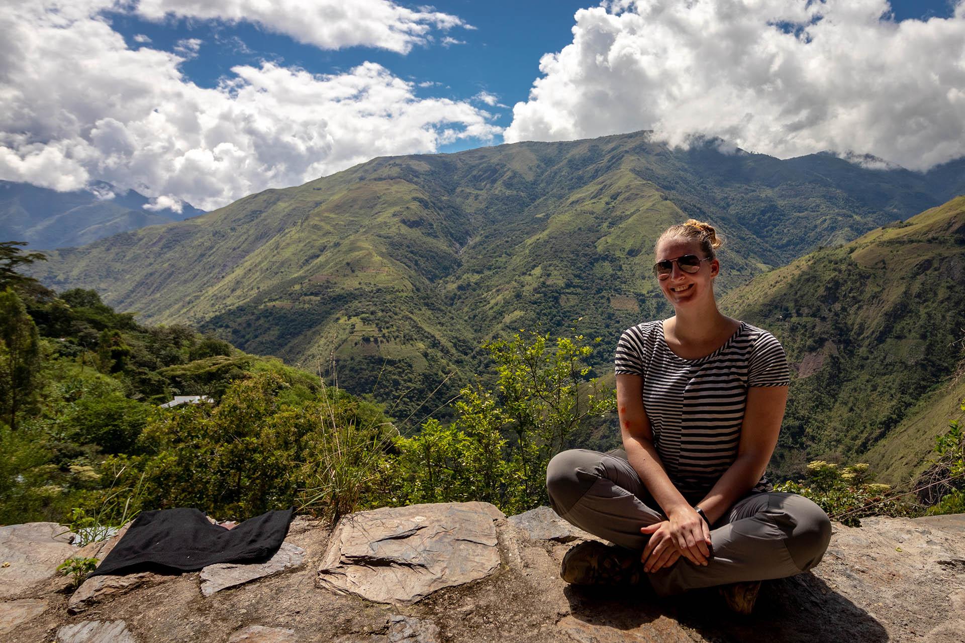 Manouk zit op een rand in het café tijdens de pauze van de wandeldag van de Inka Jungle Trek, met mooi uitzicht over een groene vallei.