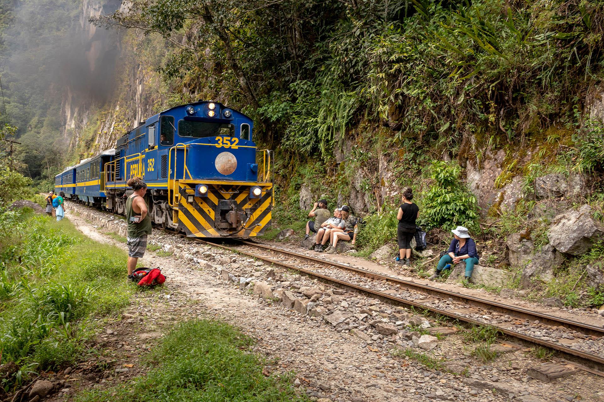 Trein van PeruRail rijdt over het treinspoor naar Aguas Calientes en mensen lopen langs het spoor.