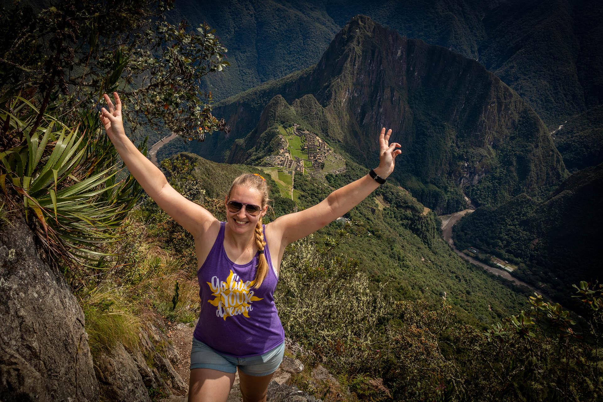 Manouk met haar armen in de lucht op Machu Picchu Mountain met achter haar in de diepte Machu Picchu.