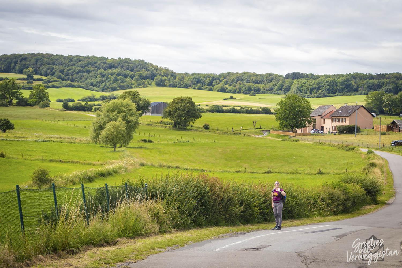Manouk op de weg naast het glooiende groene landschap in Luxemburg op de Mullerthal Trail ExtraTour A.