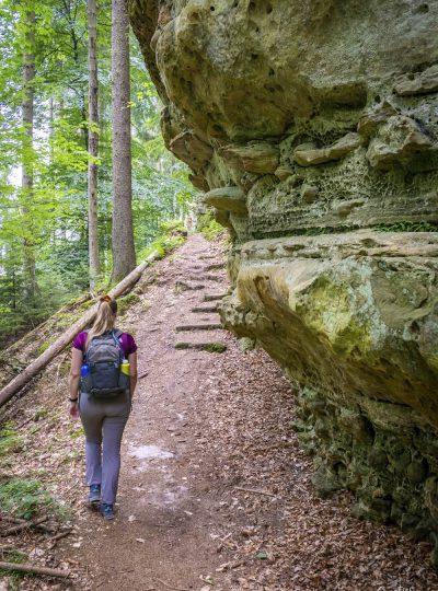 Manouk wandelt langs een rots in het bos op de Mullerthal Trail