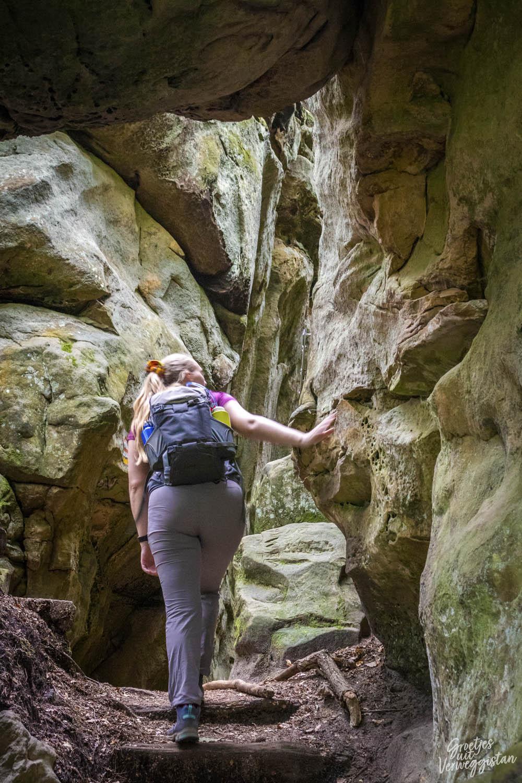 Manouk wandelt tussen smalle rotsspleten op de Mullerthal Trail