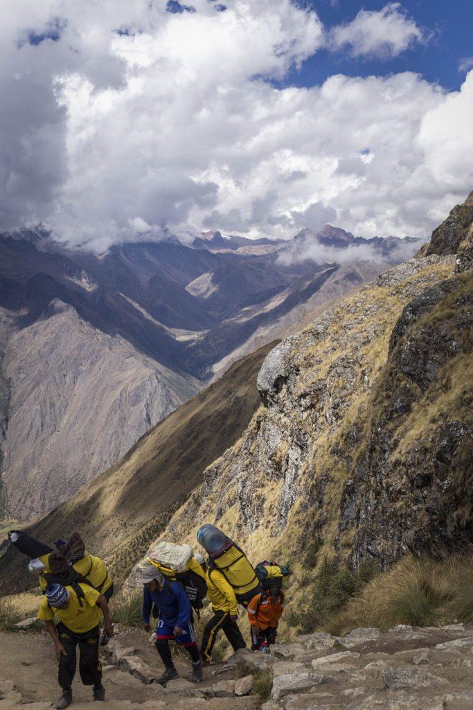 Porters klimmen de berg Dead Woman's Pass op met rugzakken vol in Peru.