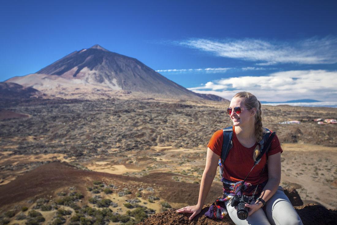 Manouk zit op een steen voor de vulkaan El Teide op Tenerife.