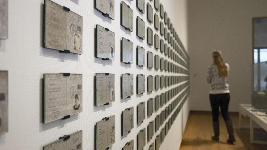 Manouk in het Fries museum bij een muur vol persoonsbewijzen uit de Tweede Wereldoorlog.