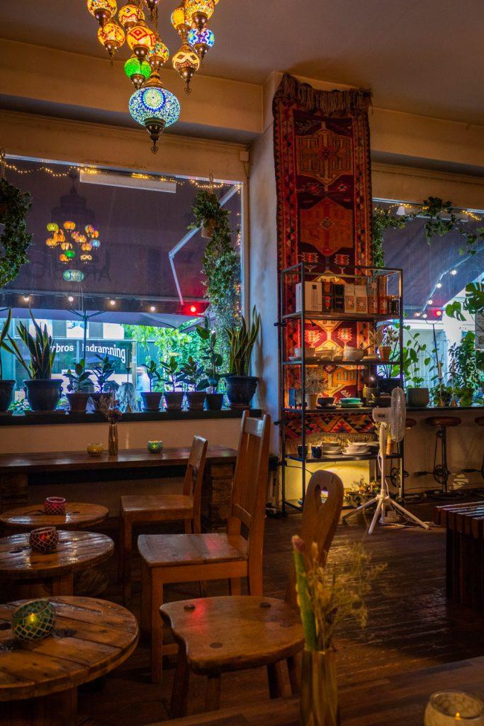 Het gezellige interieur van Arabica met mooie houten meubels en sfeervolle lampen.