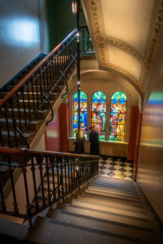 Het trappenhuis van het Museum of Copenhagen met kleurrijk glas-in-loodraam.
