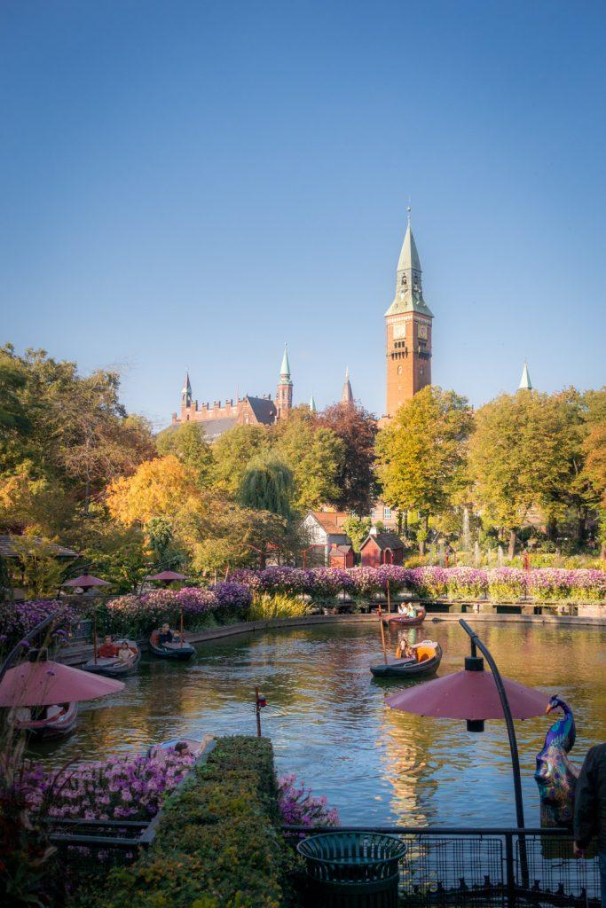 Het meer in de tuinen van Tivoli in Kopenhagen met bootjes en het stadhuis op de achtergrond.