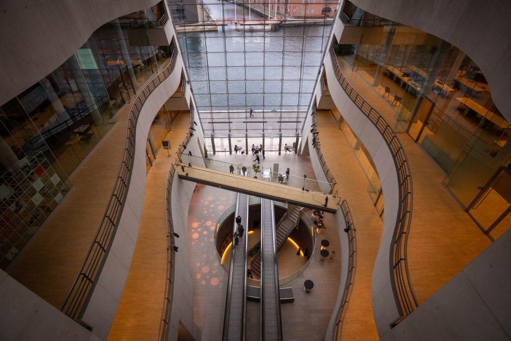 Het atrium van Black Diamond met groot glazen raam en roltrappen.