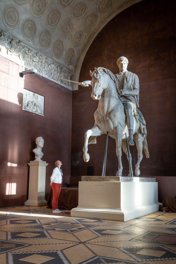Manouk kijkt naar een gigantisch ruiterstandbeeld in het Thorvaldsen's Museum.
