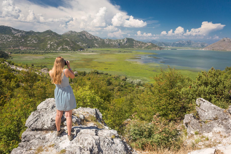 Manouk kijkt vanaf rots uit over het Skadarmeer in Montenegro met een fotocamera.