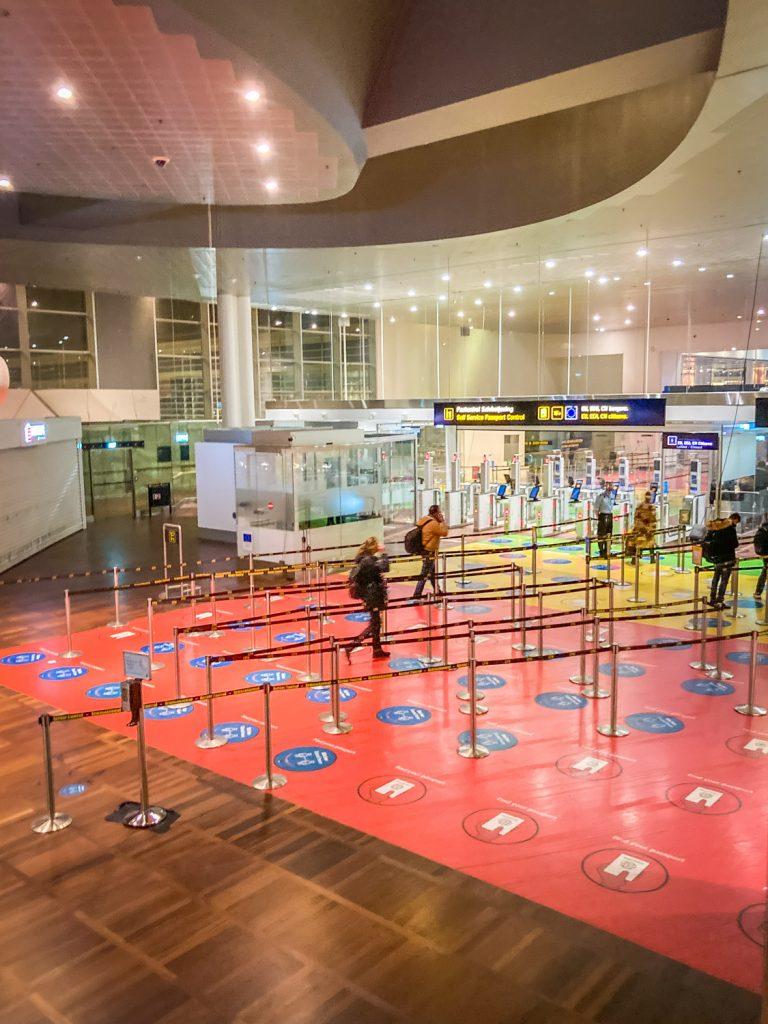 Controlepoortjes op het vliegveld van Kopenhagen met rijen met afstandstickers om het land binnen te komen.