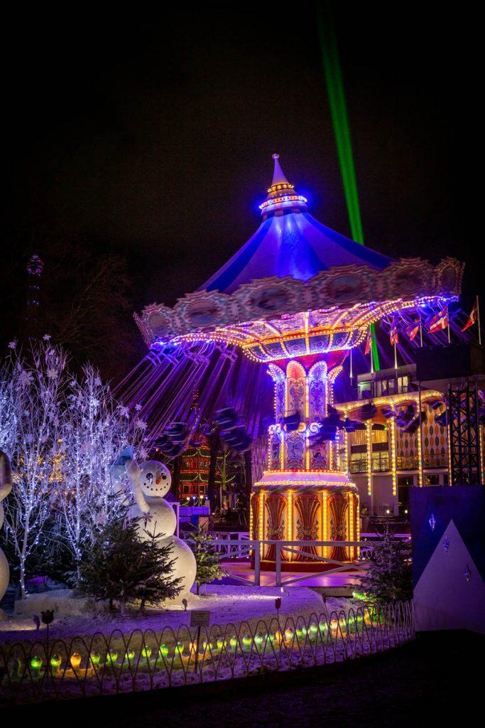 Sneeuwpop en verlichte zweefmolen in themapark Tivoli in Kopenhagen