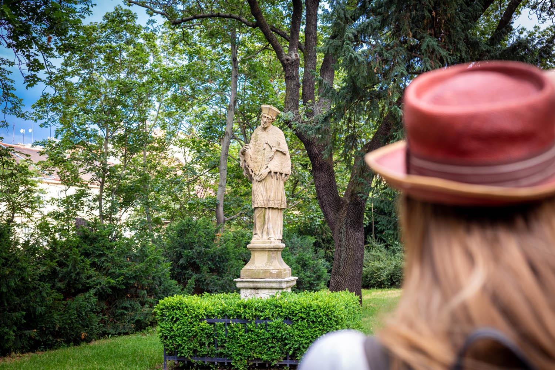 Manouk met rode hoed kijkt naar een standbeeld in het groene park bij Spilberk Castle