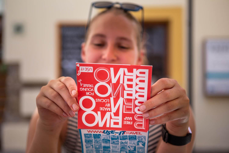 Manouk kijkt op een kaart met op de voorkant rood met witte letters Brno