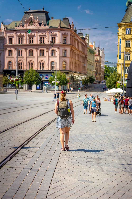 Manouk loopt over plein Namesti svobody in Brno met roze en gele gebouwen op de achtergrond