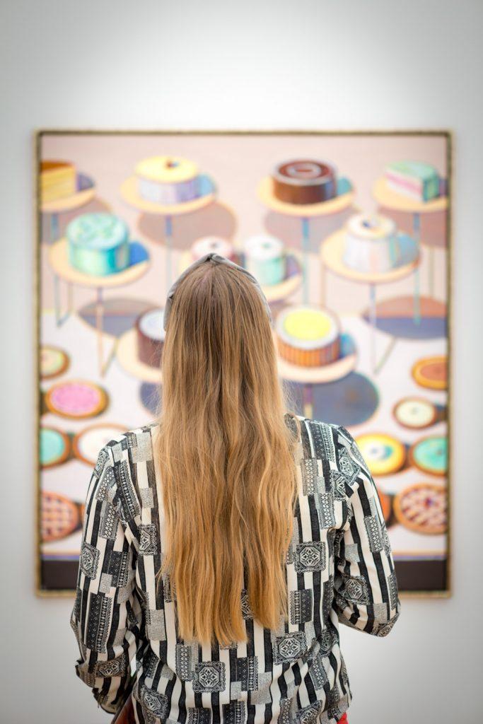 Manouk met lang blond haar voor een schilderij van taartjes in Museum Voorlinden