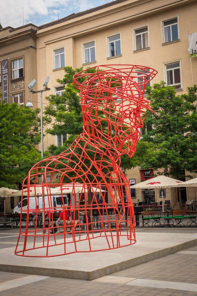 Opvallend beeld van rode draden in de vorm van een mannenbuste op straat in Brno