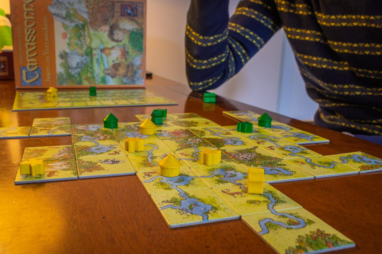 Carcassonne Jagers en Verzamelaars ligt op tafel: speelkaarten en pionnen op een uitgestald bord