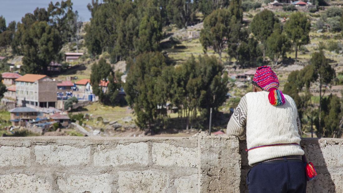 Man met gebreide roze muts leunt tegen een muurtje op het eiland Taquile in het Titicacameer