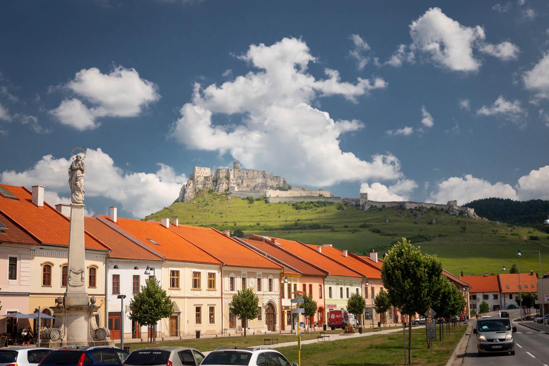 Kasteel Spišský hrad torent uit over het dorp Spis met gekleurde huizen