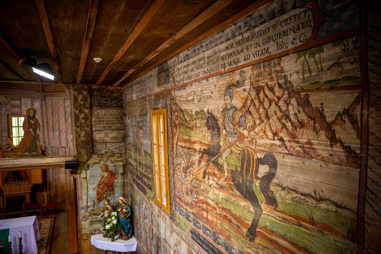 Schildering van Joris en de Draak op de houten muren van de houten kerk in Hervartov