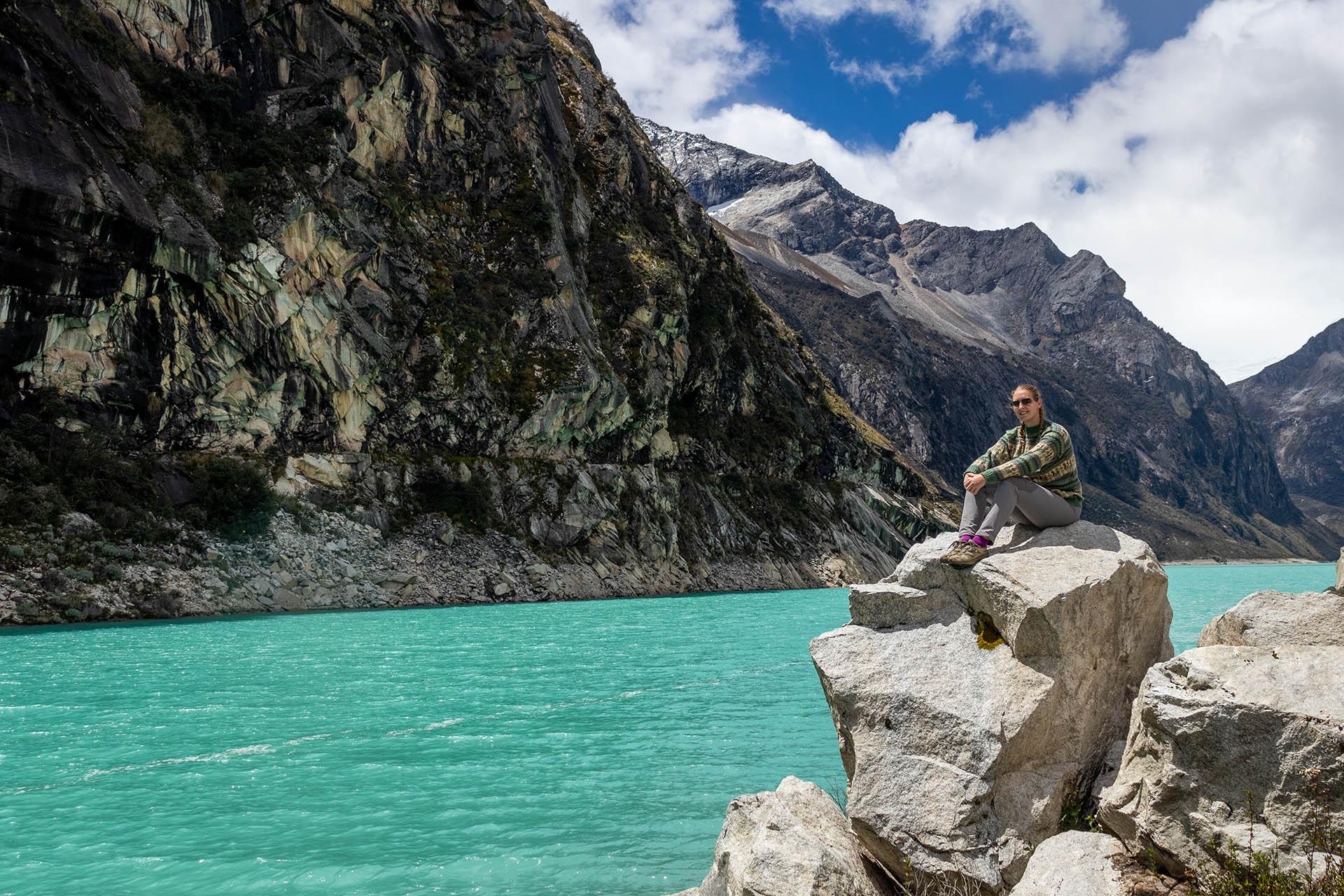 Manouk op een rots naast het felblauwe water van Laguna Paron in Peru