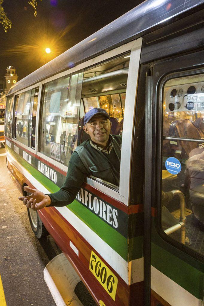 Gekleurde roodgroene bus in Lima met een man die uit het raam hangt om mensen over te halen mee te gaan