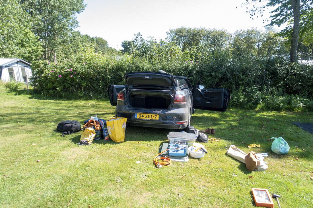 Cabrio met open deuren en kofferbak met kampeerspullen eromheen