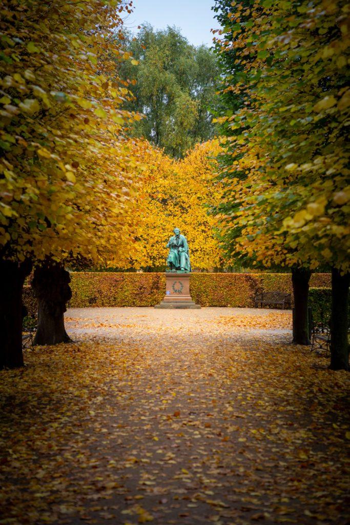 Standbeeld van Hans Christian Andersen tussen de herfstblaadjes op een open plek in Kongens Have in Kopenhagen