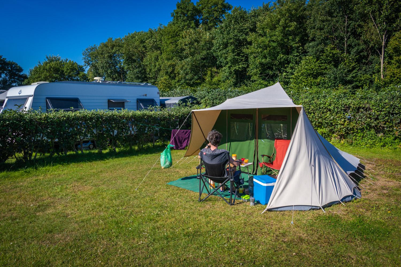 De Waard tent opgezet op een grasveld op een camping met Hugo op een stoel ervoor