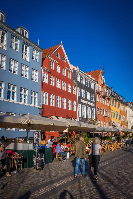 Gekleurde huisjes in Nyhavn op een zonnige dag met mensen op de kade